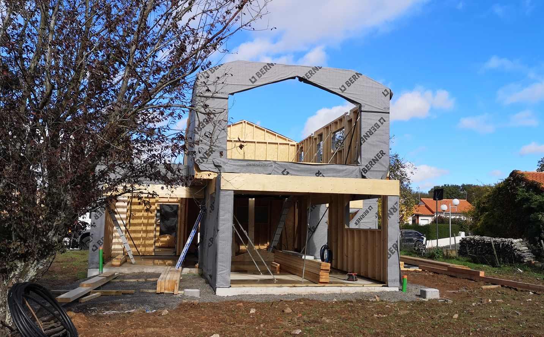 Construction d'une maison à ossature bois avec bardage en aluminium et murs enduits